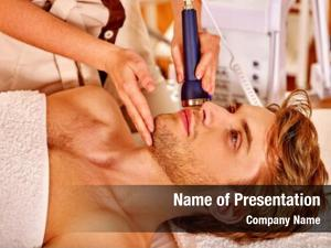 Relaxed young man luxuriating on electroporation  facial therapy at beauty salon