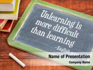 Unlearning is more difficult than learning - English proverb on a slate blackboard with a white chalk and a stack of books against rustic wooden table