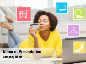 People, internet bank, online shopping, technology and e-money concept - happy african american young woman lying on floor with laptop computer and credit card at home over internet icons