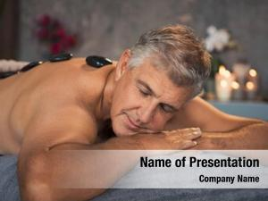 Mature man relaxing on bed during hot stone massage