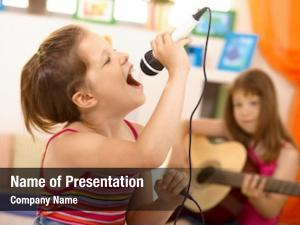 Young girl singing with microphone at home, concentrating, other girl playing guitar in