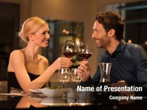 Romantic young couple at restaurant raising a toast