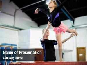 Young coach training gymnast balance