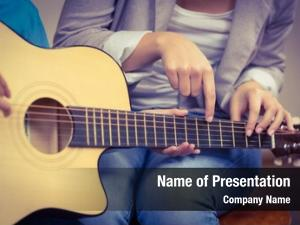 Guitar teacher giving lessons pupil