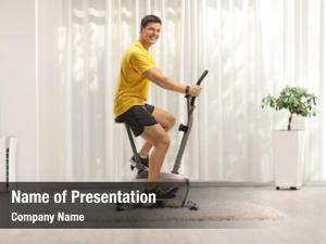 Exercising young man stationary bike