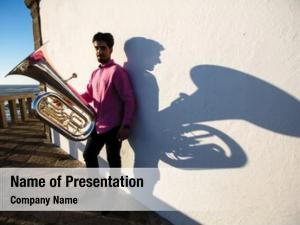 Tuba man play near white