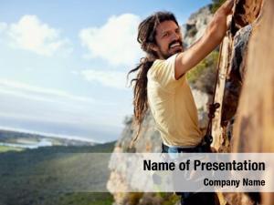 Man rock climbing dreadlocks smiling