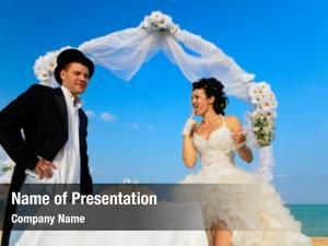 Under bride groom archway beach